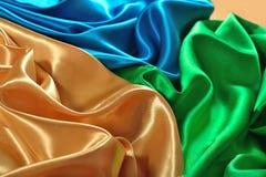 Natural golden, blue and green satin fabric texture stock image