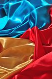 Natural golden, blue and red satin fabric texture. Natural golden, blue and red satin fabric as background texture Royalty Free Stock Photos