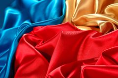 Natural golden, blue and red satin fabric texture. Natural golden, blue and red satin fabric as background texture Royalty Free Stock Photo