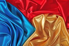 Natural golden, blue and red satin fabric texture. Natural golden, blue and red satin fabric as background texture Stock Photo