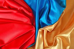 Natural golden, blue and red satin fabric texture. Natural golden, blue and red satin fabric as background texture Stock Photography