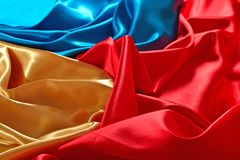 Natural golden, blue and red satin fabric texture. Natural golden, blue and red satin fabric as background texture Royalty Free Stock Images
