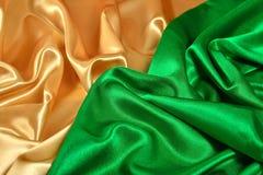 Natural golden and green satin fabric texture stock image