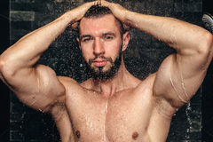 Natural goodlooking athlete showering. Muscular fitness player taking a shower Royalty Free Stock Image