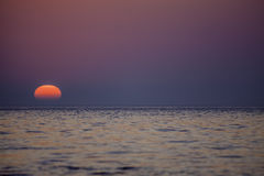 Natural Graduated Blue Purple Pink Sunrise. This perfect sunrise over a calm sea was took n a naturally red pink and purple hue due to the filter of a  low bank Royalty Free Stock Image
