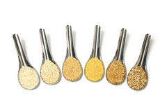 Natural grains isolated on spoons - rice quinoa couscous bulgur millet buckwheat Royalty Free Stock Photography