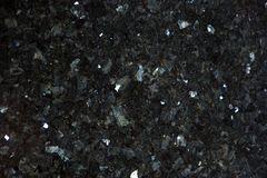 Natural granite of black color with bright glitters on the surface is called Emerald Pearl. Abstract background royalty free stock image