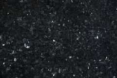 Natural granite of dark color with bright glitters on the surface, called Emerald Pearl. Abstract background stock images