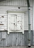 Natural grey and white old house wall with wood closed up white window, mailbox and tin waterpipe. Natural grey and white colors grunge vintage background Royalty Free Stock Image