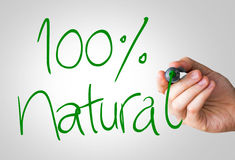 100% Natural hand writing with a green mark on a transparent board.  royalty free stock image