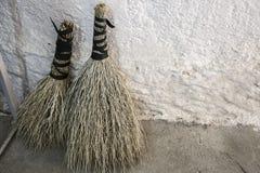 Natural handmade brooms near white plain wall stock photography