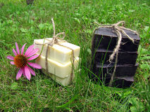 Natural handmade Castilian and tar soap bandaged with string on. Natural handmade Castilian and tar soap on grass background. Soap bars lined with stack and Royalty Free Stock Image