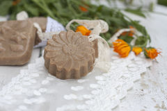 Natural handmade soap with calendula on a light background. Royalty Free Stock Images