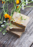 Natural handmade soap with calendula on a light background. Stock Photos