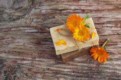 Natural handmade soap with calendula (pot marigold). On rustic wooden background Stock Photos