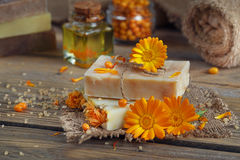 Natural handmade soap with calendula (pot marigold) and sea-buck. Thorn on rustic wooden background Royalty Free Stock Photos