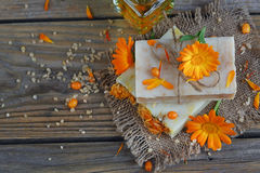 Natural handmade soap with calendula (pot marigold) and sea-buck. Thorn on rustic wooden background Royalty Free Stock Image