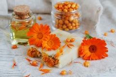 Natural handmade soap with calendula and sea buckthorn. Natural handmade soap with calendula (pot marigold) and sea-buckthorn on white wooden background Stock Photo
