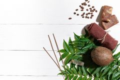 Natural handmade soaps with coffee beans, brown towel, coconut and green leaves on white wooden background Stock Photo