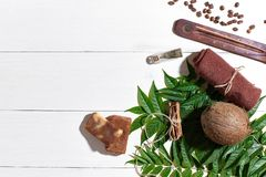 Natural handmade soaps with coffee beans, brown towel, coconut and green leaves on white wooden background Royalty Free Stock Photos