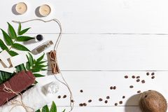 Natural handmade soaps with coffee beans, cinnamon, candles, oil, brown towel, coconut and green leaves on white wooden Royalty Free Stock Photos