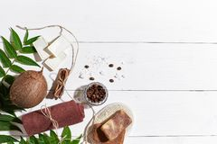 Natural handmade soaps with coffee beans, cinnamon, sea salt, loofah, brown towel, coconut and green leaves on white Stock Photography