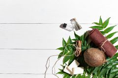 Natural handmade soaps with oil, brown towel, coconut and green leaves on white wooden background Royalty Free Stock Photo