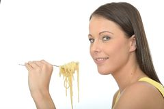 Natural Happy Young Woman Eating A Fork Full of Cooked Spaghetti Pasta Stock Photo