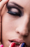 Natural health beauty of a woman face. Close-up eye with dark make-up. Natural health beauty of a woman face. Multicolored make-up royalty free stock photo