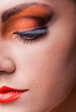 Natural health beauty of a woman face. Close-up orange eyes make-up. Natural health beauty of a woman face. Multicolored make-up Royalty Free Stock Images