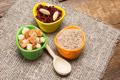 Natural health products with wooden spoon. On burlap napkin. Ceramic cups filled with wheat bran, mixtures of nuts with dried fruits and berries. Peeled royalty free stock photography