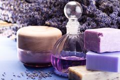 Natural healthy aromatherapy and skin treatment with organic French lavender, lavender soap, body cream and essential oils on. Purple background with dried stock image