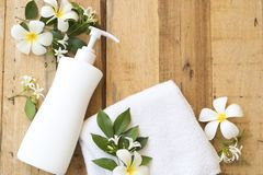 Natural herbal liquid soap health care for body skin. With terry cloth ,flower frangipani arrangement flat lay style on background wooden stock photography