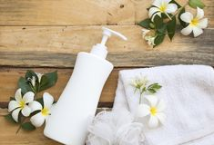 Natural herbal liquid soap health care for body skin. With terry cloth ,flower frangipani arrangement flat lay style on background wooden royalty free stock images