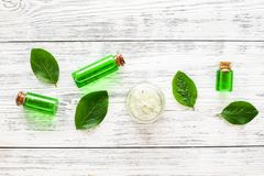 Natural hipoallergenic cosmetics with tea tree essential oil. Oil, lotion, leaves on white wooden background top view royalty free stock photo
