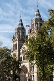 Natural History Museum of London, United Kingdom with British flag on a sunny day. royalty free stock image