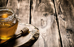 Natural honey in glass jar. Natural honey in a glass jar on a wooden trunk. On wooden background Stock Images