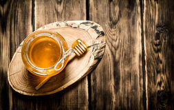 Natural honey in glass jar. Natural honey in a glass jar on a wooden trunk. On wooden background Stock Photos