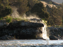 Natural hot springs above a river on the bank Stock Image