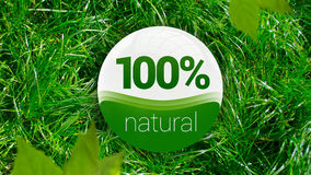 100% Natural icon. 100% Natural and eco icon laying on the green grass Royalty Free Stock Image