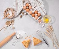 Natural ingredients for baking. Top view of baking ingredients and some pieces of cake on kitchen table  on grey backround Royalty Free Stock Photography