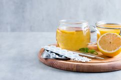 Natural ingredients for cough remedy on wooden table. Lemon, honey, tea, mint and tablets. Top view, space for copy. Natural ingredients for cough remedy on Stock Image