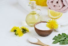 Natural ingredients for homemade body salt scrub with dandelion flowers, lemon, honey and olive oil. Natural ingredients for homemade body face hair salt scrub Stock Photography
