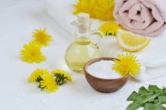 Natural ingredients for homemade body salt scrub with dandelion flowers, lemon, honey and olive oil. Natural ingredients for homemade body face hair salt scrub Stock Photo