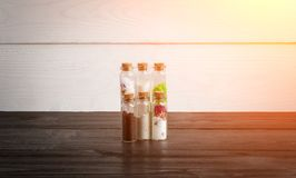 Natural ingredients for skin care on wooden background. Sun flare. Natural ingredients for skin care on wooden background. Sea salt, ground oatmeal and coffee Stock Images