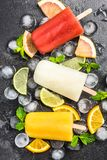 Natural juice homemade healthy popsicles over ice cubes. Background citrus cold colorful concept cool copyspace dark delicious dessert flat lay flavor flavored stock image