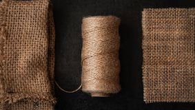 Natural jute twine roll, burlap on black background. Supplies and tools for handmade hobby leisure. Closeup stock photo