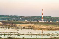 Natural lake is a chalky quarry with a factory smokestack under a green hill on the horizon Stock Images