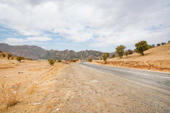 Natural landscape with an asphalt road between the villages surrounded by mountains Stock Photo