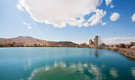 Natural landscape with cloudy sky over the historical persian ruined city and clear water of a mountain lake Royalty Free Stock Photo